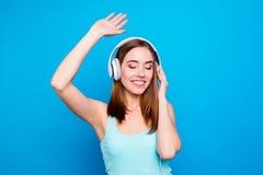 Portret śmieszny śliczny dosyć nastoletni nastolatek ma weekendy używać technologii słuchawki przesłuchania faworytów ubierającyc zdjęcie stock