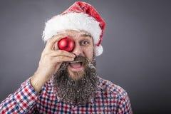 Portret śmieszny brodaty mężczyzna jest ubranym Santa nakrętkę i trzyma a Fotografia Stock