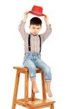 Portret śmieszny chłopiec obsiadanie na wysokiej stolec w czerwieni Zdjęcie Stock