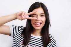 Portret śmieszny kobieta model patrzeje joyfully przy kamerą, gestykuluje z palcami, szczęśliwego wyrażenie, robi zabawie, pozy fotografia stock