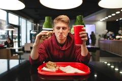 Portret śmieszny młodego człowieka łasowania fast food przy tłem restauracja obraz stock