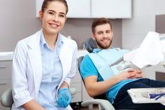 Portret żeński dentysta młody szczęśliwy męski pacjent i zdjęcie stock
