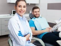 Portret żeński dentysta młody szczęśliwy męski pacjent i Fotografia Royalty Free
