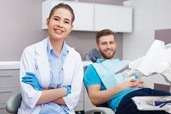 Portret żeński dentysta młody szczęśliwy męski pacjent i Zdjęcia Royalty Free