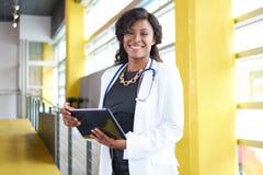 Portret żeński doktorski mienie jej cierpliwa mapa na cyfrowej pastylce w jaskrawym nowożytnym szpitalu obrazy stock