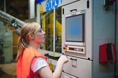 Portret żeński pracownik w pomarańczowej kontusz kamizelce w pracującej przestrzeni zakład wytwórczy, dogląda li i kontroluje zdjęcie stock