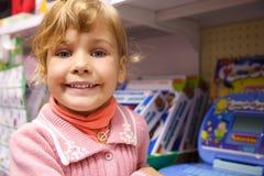 Portret aan meisje tegen show-venster van speelgoed stock foto's