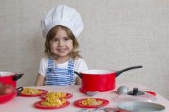 Portret Aanbiddelijk meisje in de kokvoedsel van de chef-kokhoed Stock Fotografie