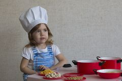 Portret Aanbiddelijk meisje in de kokvoedsel van de chef-kokhoed Royalty-vrije Stock Foto's