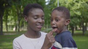 Portret aanbiddelijke Afrikaanse Amerikaanse vrouw die haar grappige zoon in haar wapens in het groene park dicht tegenhouden Leu stock videobeelden