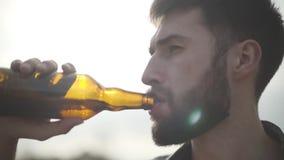 Portret aantrekkelijk gebaard mens het drinken bier en in openlucht het genieten van van drank De kerel proeft lagerbier van fles stock footage