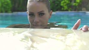 Portret aantrekkelijke vrouw in zwembad die en aan camera stellen kijken Sluit gezichts omhoog het jonge vrouw zwemmen in openluc stock footage