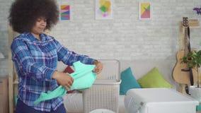 Portret Afrikaanse Amerikaanse huisvrouw in overhemd die thuiswerk doen, die uitgewassen kleren thuis nemen stock footage