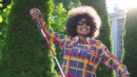 Portret Afrikaanse Amerikaanse vrouw blind met een afrokapsel met een riet, langzame mo van de zonstraal stock videobeelden