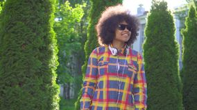 Portret Afrikaanse Amerikaanse vrouw blind met een afrokapsel met een riet, zonstraal stock videobeelden