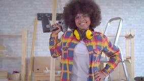Portret Afrikaanse Amerikaanse vrouw met timmerman van het afrokapsel in een moderne workshop stock footage