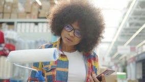Portret Afrikaanse vrouw met een afrokapsel met de telefoon in hand in de winkel in de afdeling allen voor reparatie stock videobeelden