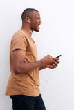 Portret afro amerykańskiego mężczyzna słuchająca muzyka przeciw białemu tłu Obrazy Royalty Free