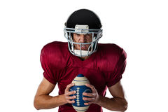 Portret agresywny futbolu amerykańskiego gracz jest ubranym hełma mienia piłkę Zdjęcie Royalty Free