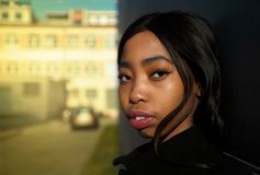 Portret amerykańska Afrykańska młoda kobieta z plama samochodem w miasto ulicie i budynkiem obraz stock