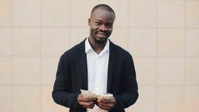 Portret amerykanin afrykańskiego pochodzenia biznesmen stoi blisko biurowego centre w kostiumu odliczającym pieniądze On świętuje zbiory wideo