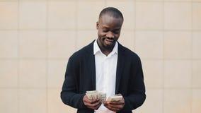 Portret amerykanin afrykańskiego pochodzenia biznesmen stoi blisko biurowego centre w kostiumu odliczającym pieniądze On świętuje zdjęcie wideo