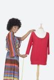 Portret amerykanina afrykańskiego pochodzenia żeński projektant mierzy czerwoną tunikę nad szarym tłem Obraz Stock