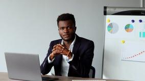 Portret amerykanina afrykańskiego pochodzenia mężczyzna obsiadanie przy laptopem w biurze w kostiumu i białej koszula na tle wykr zbiory wideo