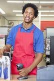 Portret amerykanina afrykańskiego pochodzenia sprzedawcy męska pozycja przy kasa kontuarem Fotografia Stock