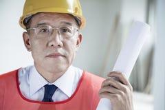 Portret architekt trzyma staczający się w górę projekta indoors w hardhat, zakończenie Zdjęcia Stock