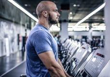 Portret atleta na kieratowym słuchaniu muzyka Wyczerpuje i myśleć o coś, on ciężkiego trening obrazy royalty free