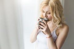 Portret atrakcyjna blond kobiety pozycja blisko okno z herbatą lub filiżanka kawy zdjęcie stock