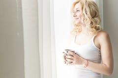 Portret atrakcyjna blond kobiety pozycja blisko okno z herbat? lub fili?anka kawy obraz royalty free