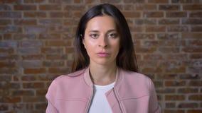 Portret atrakcyjna caucasian brunetka patrzeje kamerę prosto i spokojnie stoi blisko czerwonego ściana z cegieł