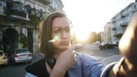 Portret atrakcyjna dziewczyna z outstreched ręką pozuje dla kamery, koryguje jej krótkiego włosy Hełmofony na jej szyi zbiory