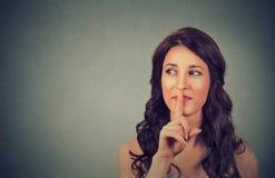 Portret atrakcyjna nastoletnia dziewczyna z palcem na wargach, pojęcie studencka przedstawienie zaciszność, cisza, tajny gest, mł Zdjęcie Royalty Free