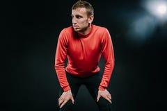 Portret atrakcyjna rozważna mężczyzna atleta relaksuje po ciężkiego treningu przy gym, stawia jego rękę na nogach opierać Zdjęcia Stock