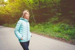 Portret atrakcyjna sport dziewczyny blondynka w lekkiej bieg puszka kurtki bluetooth opatrunkowych hełmofonach z muzyką lub Obraz Stock