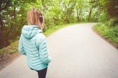 Portret atrakcyjna sportowa blondynki dziewczyna zaświecać bieg puszka kurtkę od z powrotem, jest ubranym bluetooth hełmofony z Zdjęcie Stock