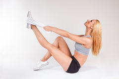 Portret atrakcyjna sportowa caucasian kobieta z długim blondynem odizolowywającym na szarym studiu strzelał z ręcznikowym rozciąg Fotografia Stock