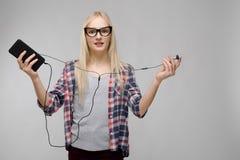Portret atrakcyjna uśmiechnięta słodka urocza blondynka nastolatka dziewczyna trzyma telefon komórkowego w w kratkę odziewa w szk Obrazy Stock