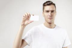 Portret atrakcyjnego biznesmena mienia pusta wizytówka, opróżnia przestrzeń dla układu, z białym tłem Ostrość na karcie Obrazy Stock