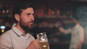 Portret atrakcyjnego mężczyzny pijącego piwo i patrzącego na kamerę w barze lub pubie piwnym Pojęcie młodzieży, przyjaźni i zbiory wideo