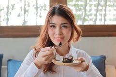 Portret atrakcyjnego młodego Azjatyckiego kobiety łasowania punktu czekoladowy tort w kawowej kawiarni Obraz Stock