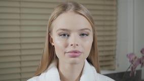 Portret atrakcyjni uśmiechnięci kobieta blondyny W białym bathrobe po procedury Kosmetologia i zdroju centrum pojęcie zdjęcie wideo