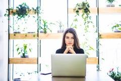 Portret atrakcyjny biznesowej kobiety obsiadanie w chait i działanie przy laptopem online zdjęcia royalty free