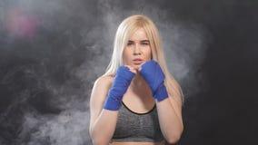 Portret atrakcyjny blondynki kobiety wojownik w boksie bandażuje pozować w obrończej bokser postawie zdjęcie wideo