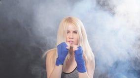 Portret atrakcyjny blondynki kobiety wojownik w boksie bandażuje pozować w obrończej bokser postawie, zwolnione tempo zbiory wideo
