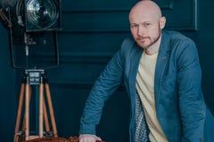 Portret atrakcyjny dorosły pomyślny łysy brodaty mężczyzna w kostiumu na błękitnym tle, blogging, TV gospodarz obraz royalty free