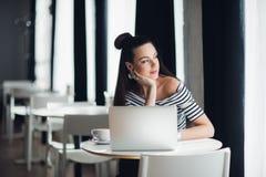 Portret atrakcyjny kobiety obsiadanie w niektóre sklep z kawą z jej laptopem i główkowanie nad tematem podczas gdy patrzejący Obraz Stock